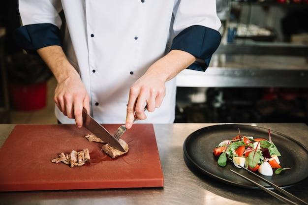Koken gesneden geroosterd vlees aan boord in de buurt van salade