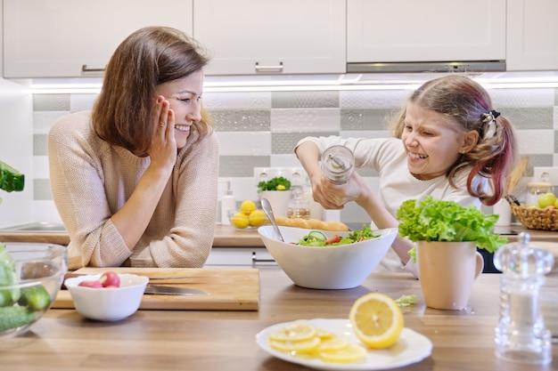 Koken gezond thuis maaltijd door familie. meisje zouten vers gekookte salade, moeder kijkt op en verheugt zich