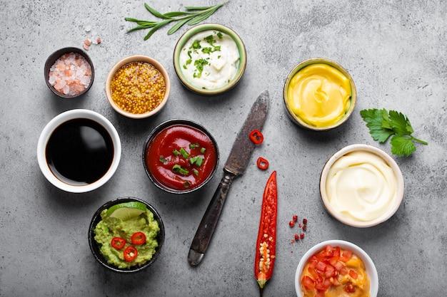 Koken gezonde sauzen en dressings concept. verschillende dips in kommen op rustieke betonnen ondergrond, ingrediënten, kruiden, peper, chili en keukenmes, bovenaanzicht, close-up