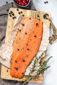 Koken gezouten zeeforelfilet op een houten snijplank met kruiden en specerijen