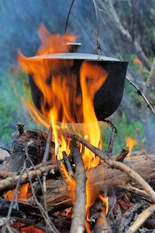 Koken in de natuur. ketel in brand in bos
