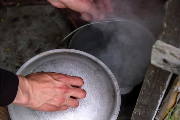 Koken in een gietijzeren ketel op een driepoot boven een open vuur. selectieve focus