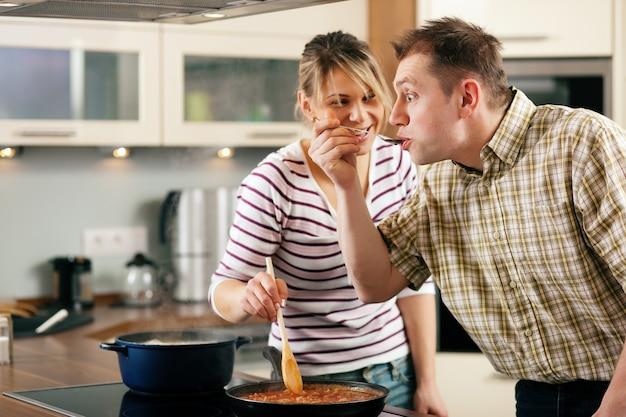 Koken in familie die de saus proeft