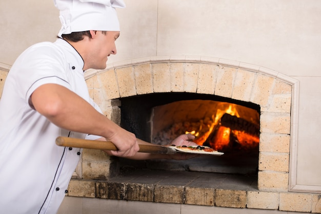 Koken in witte uniform plaatst een gerecht in de oven.