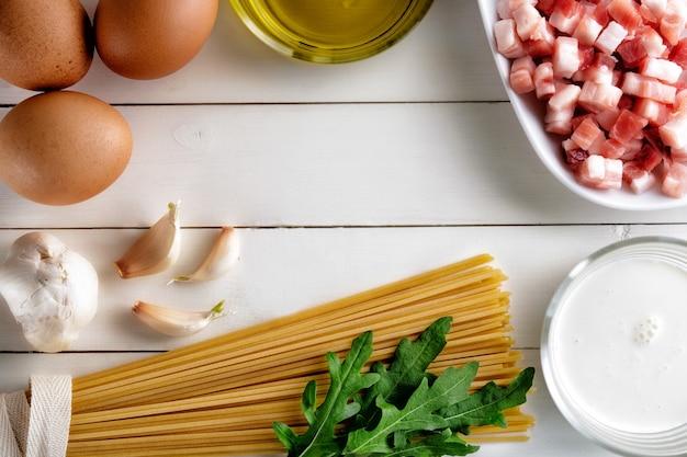 Koken ingrediënten voor carbonara op rustieke ondergrond.