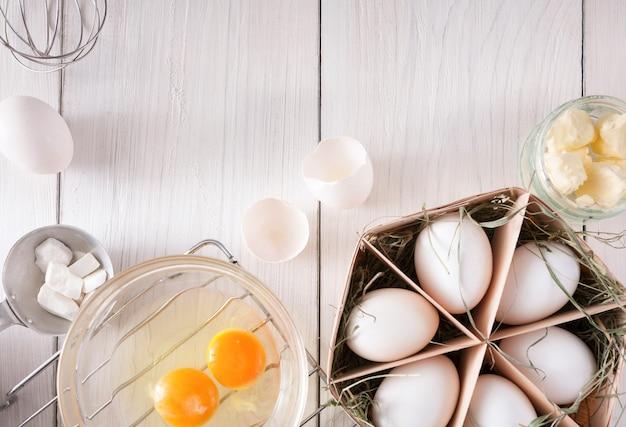Koken ingrediënten voor deeg en gebak, eierdooiers, bloem op wit rustiek hout.