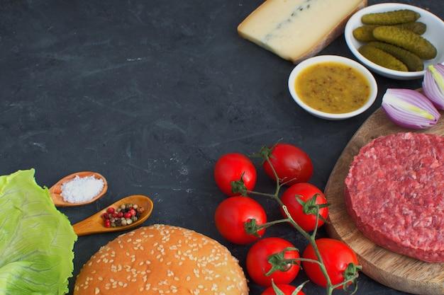 Koken ingrediënten voor het koken hamburgers hamburger voorbereiding houten snijplank zwarte achtergrond