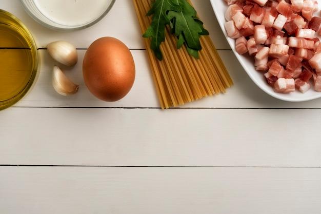 Koken ingrediënten voor italiaanse carbonara op rustieke ondergrond. pasta, spaghetti met pancetta, ei, spek, room, knoflook, rucola, olijfolie.