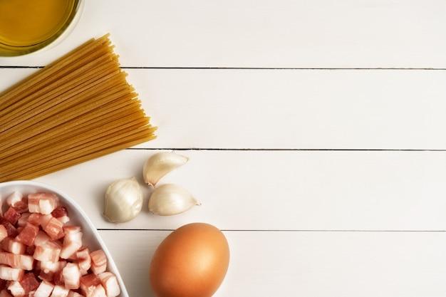 Koken ingrediënten voor italiaanse carbonara op rustieke ondergrond.