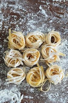Koken italiaanse zelfgemaakte pasta op donkere achtergrond