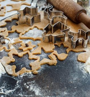 Koken kerstkoekjes met cookie cutters op een donkere tafel