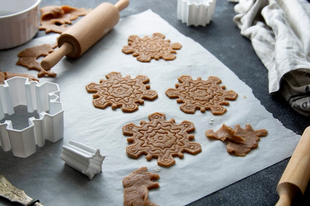 Koken kerstkoekjes sneeuwvlokken vorm. rauw deeg, koekjesmessen, deegroller.