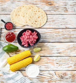 Koken mexicaanse taco-ingrediënten met gehakt biologisch rundvlees in zwarte kom