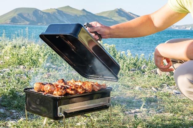 Koken op de barbecue. buitenshuis. dichtbij zee, strand en bergen