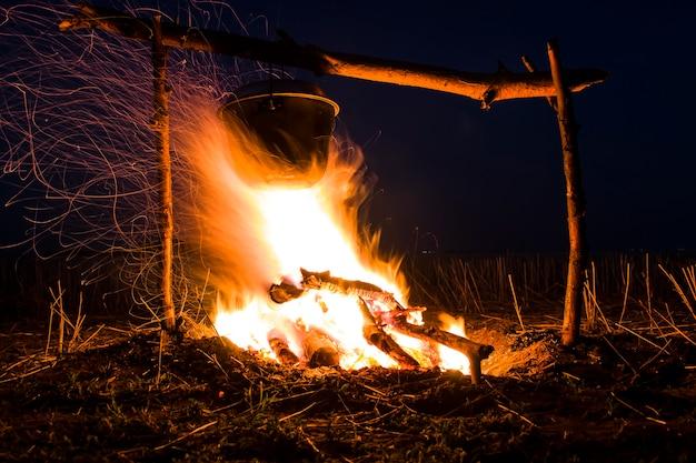 Koken op het vuur voor een kampeertrippot boven een vuur buiten de romantiek van het wilde toerisme en ...