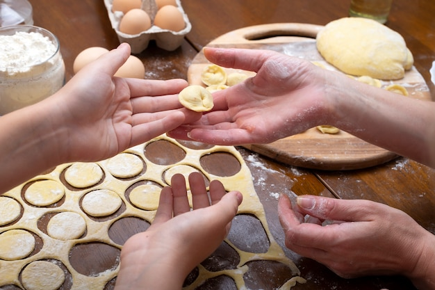 Koken ravioli van deeg en vlees met het hele gezin. dames- en kinderhanden. zelfgemaakte knoedels.