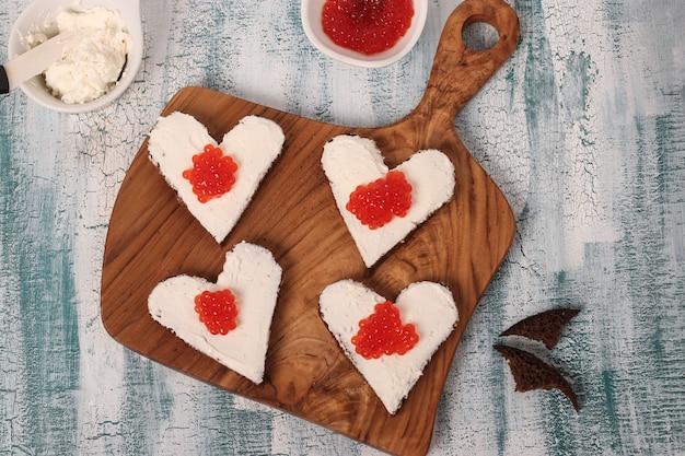 Koken sandwiches met rode kaviaar en roomkaas in de vorm van een hart voor valentijnsdag, bovenaanzicht