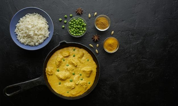 Koken smakelijke boterkip-curryschotel met rijst in een gietijzeren pan