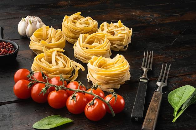 Koken tagliatelle pasta en ingrediënten set, op oude donkere houten tafel achtergrond