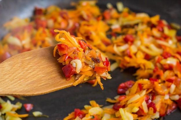 Koken van een braadstuk voor soep van uien, wortelen, paprika, tomaten, kruiden en specerijen in zonnebloemolie in een koekenpan.