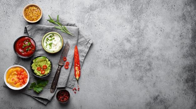 Koken van gezonde sauzen en dressings concept met kopieerruimte. verschillende dips in kommen op rustieke betonnen ondergrond, ingrediënten, kruiden, peper chili en keukenmes, bovenaanzicht, close-up sjabloon