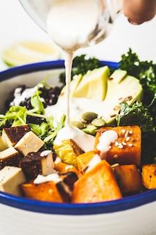 Koken van vegan salade met zwarte rijst, avocado, tofu, zoete aardappel, boerenkool en tahinidressing