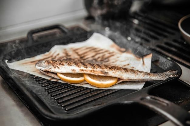 Koken van vis op een grill met citroen
