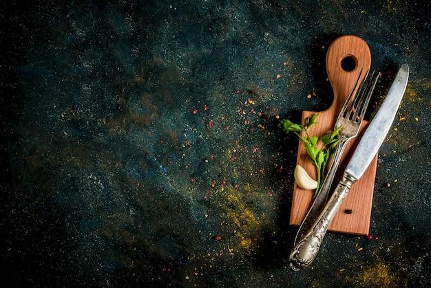 Koken voedselconcept, specerijen, kruiden en olie voor het bereiden van het diner, met snijplank
