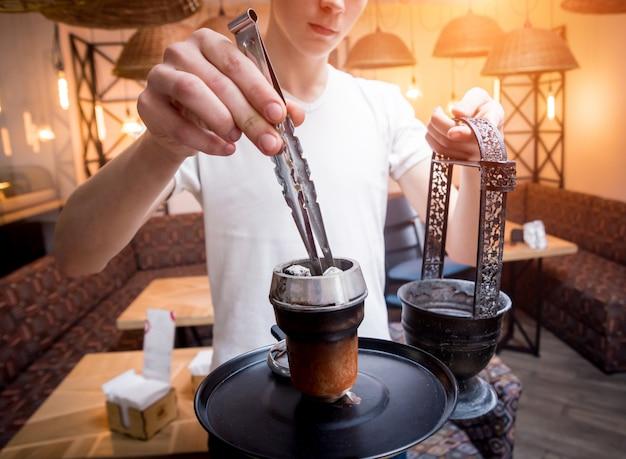 Koken waterpijp in de bar. jonge man met waterpijp in restaurant, hookah bar, roken café.