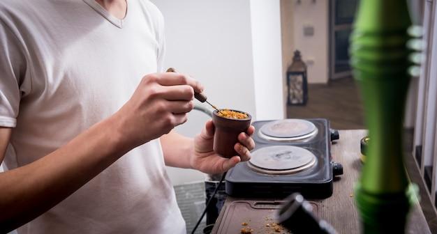 Koken waterpijp in de bar. tabak snijden in een kom. restaurant, waterpijpbar, rookcafé.