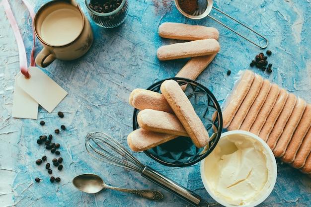 Kokend tiramisuconcept, ingrediënten voor het maken van italiaans dessert op blauwe lijst, proces van voorbereiding