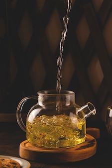 Kokend water giet in linde thee in een moderne theepot op een donkere achtergrond. minimalisme en gezonde biologische producten