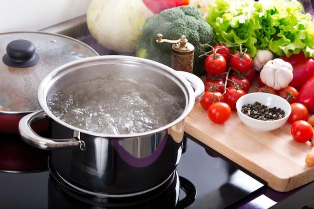 Kokend water in een kookpot op het fornuis en ingrediënten voor het koken in de keuken
