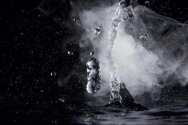 Kokend water splash met stoom op zwarte achtergrond close-up