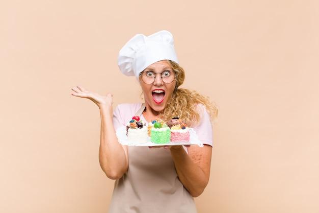 Kokende cakes van middelbare leeftijd bakkersvrouw