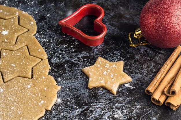 Kokende de peperkoekkoekjes van kerstmis met ingrediënten en decor op dark