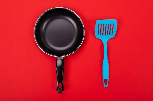 Kokende die werktuigen in keuken met copyspace op rode achtergrond wordt geïsoleerd