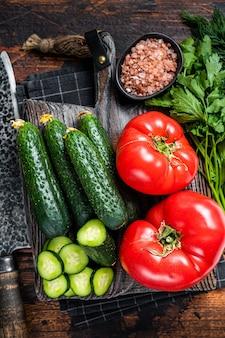 Kokende groene groentensalade met tomaten, komkommers, peterselie, kruiden. donkere houten achtergrond. bovenaanzicht.