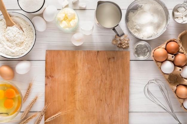 Kokende ingrediënten voor het maken van deeg en gebak en houten pizzaraad op wit rustiek hout.