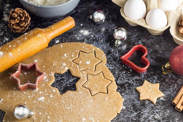 Kokende kerstmispeperkoekkoekjes met ingrediënten en decor op een donkere achtergrond