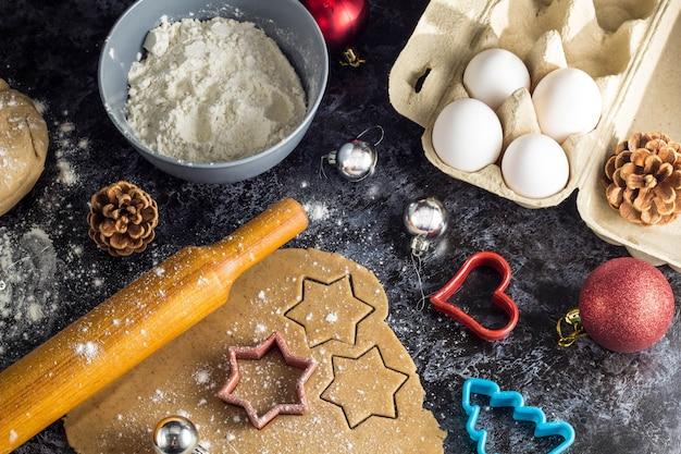 Kokende kerstmispeperkoekkoekjes met ingrediënten en decor