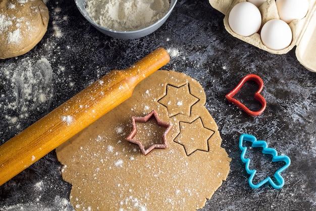 Kokende kerstmispeperkoekkoekjes met ingrediënten op een donkere achtergrond