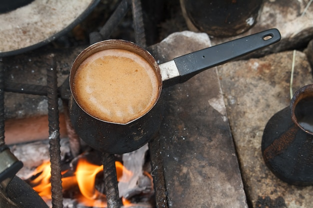 Kokende koffie in turkse cezva op een rooster boven een brandend vuur, een campingconcept