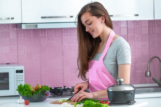 Kokende vrouw die rijpe groenten voor gezonde verse salades en schotels in keuken thuis hakken