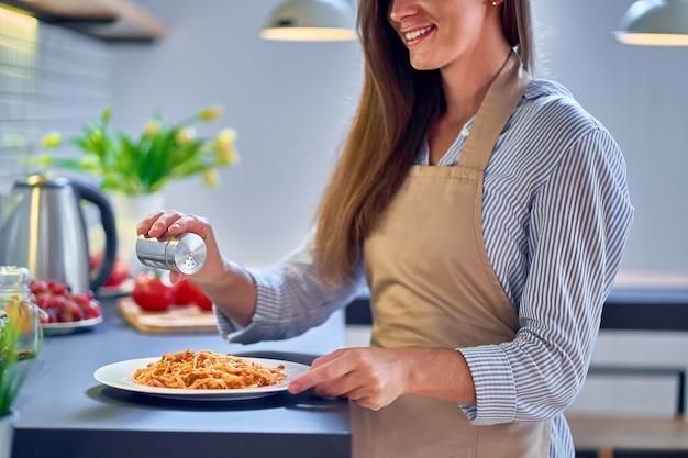 Kokende vrouwenchef-kok die schortzout draagt en voedsel voor diner voorbereidt