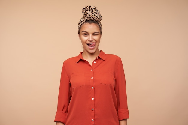 Koket jonge mooie bruinharige vrouw die vrolijk knipoogt naar voren en tong uitsteekt terwijl ze over beige muur staat in vrijetijdskleding
