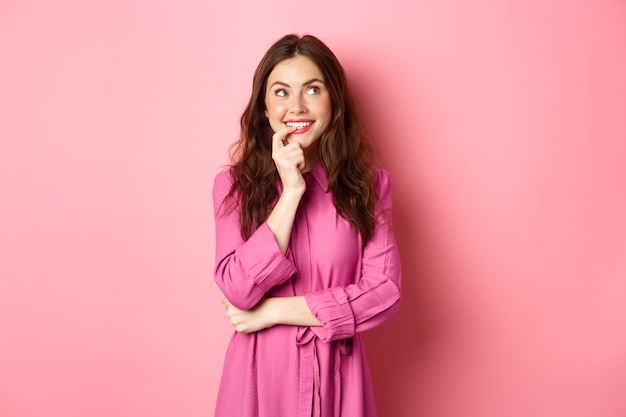 Koket jonge vrouw die bedachtzaam opzij kijkt, glimlachend en vinger bijt terwijl ze denkt, iets voorstelt, staande over roze muur.