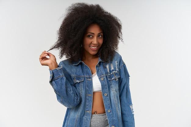Koket krullend donker gevild vrouwtje in witte top en jeansjas die met haar haar over witte muur speelt, opzij kijkend met een brede en vrolijke glimlach