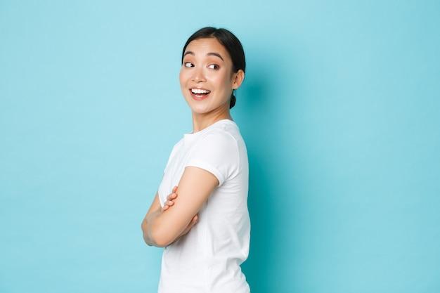 Koket mooi aziatisch meisje in wit t-shirt dat in profiel staat en naar rechts draait met nieuwsgierig lachend gezicht, kijkend naar iets interessants, goede promo-aanbieding gevonden, staande blauwe achtergrond