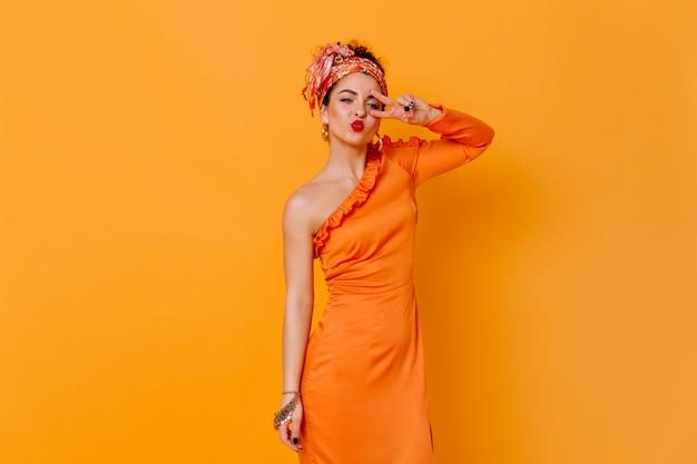Koket vrouw in zijden lange jurk en hoofdband blaast kus en toont vredesteken op oranje ruimte.